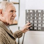 Old man, hand on calendar, staring off as though confused