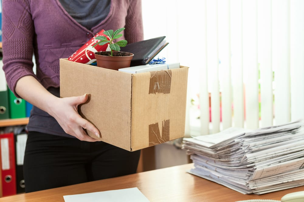 Female figure holding box of work supplies at desk, now unemployed.jpg