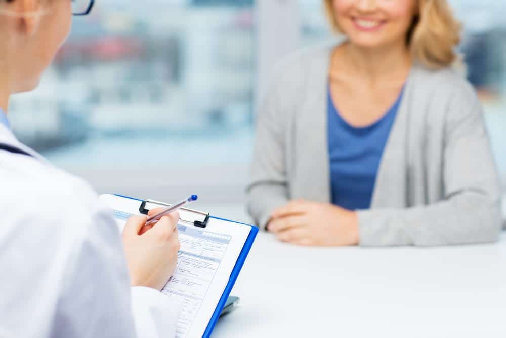Close-up of smiling woman talking to healthcare professional with clipboard form