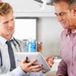 Patient sitting in doctor's office discussing something with doctor, who's using a tablet as a visual guide
