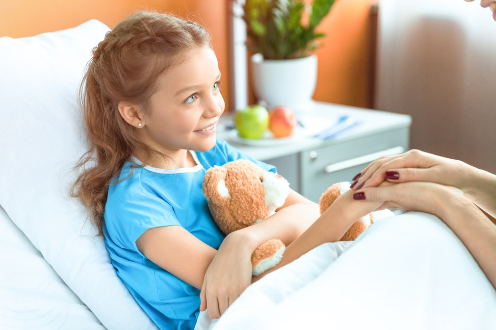 Female child patient in hospital bed, holding female adult's hand and teddy bear