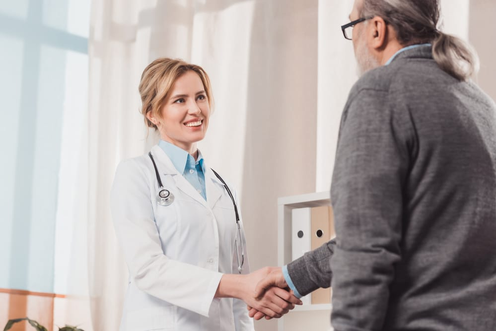 Smiling female doctor shaking hands with male patient