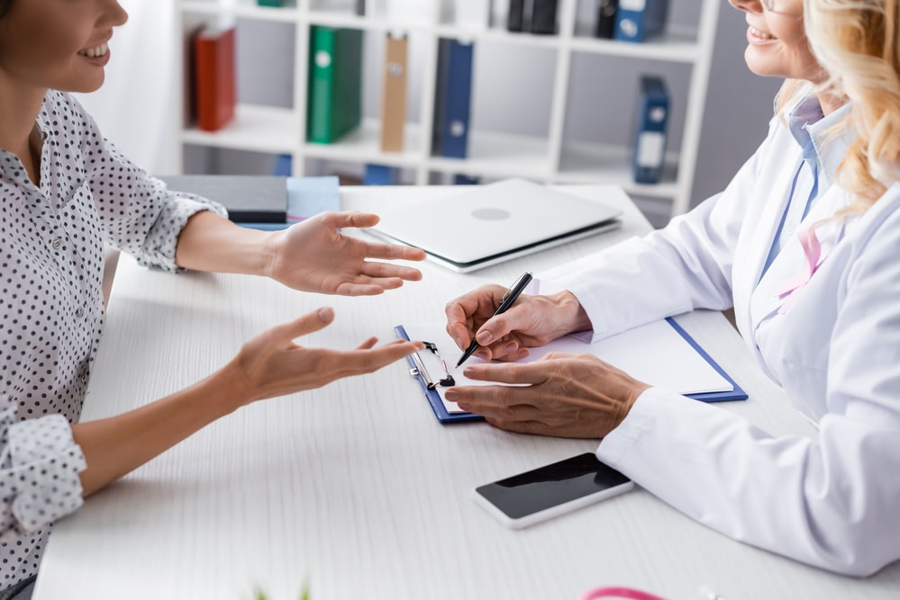 Cropped close-up of smiling female doctor and patient talking over desk