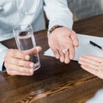 Doctor holding out glass of water and pill, patient holding out hand to accept